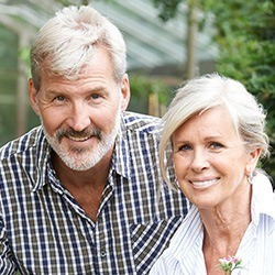 Older man and woman with healthy smiles thanks to restorative dentistry