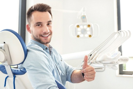 smiling man giving thumbs up in dentist's chair