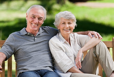 Smiling older man and woman with dentures on park bench