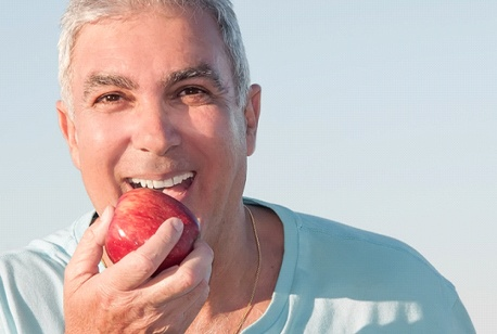 Older man biting an apple after full mouth reconstruction.
