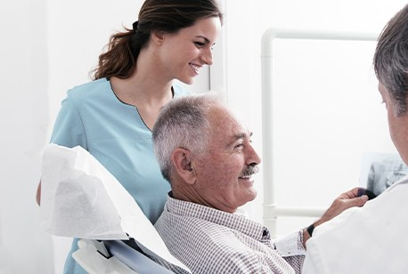 Older man in dental office discussing full-mouth reconstruction options