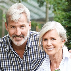Older man and woman with healthy smiles thanks to periodontal therapy