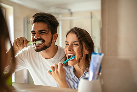 Man and woman brushing teeth to preserve teeth whitening results