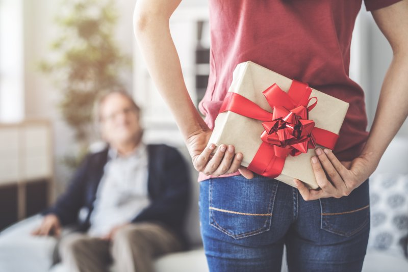 Closeup of woman hiding gift from family member